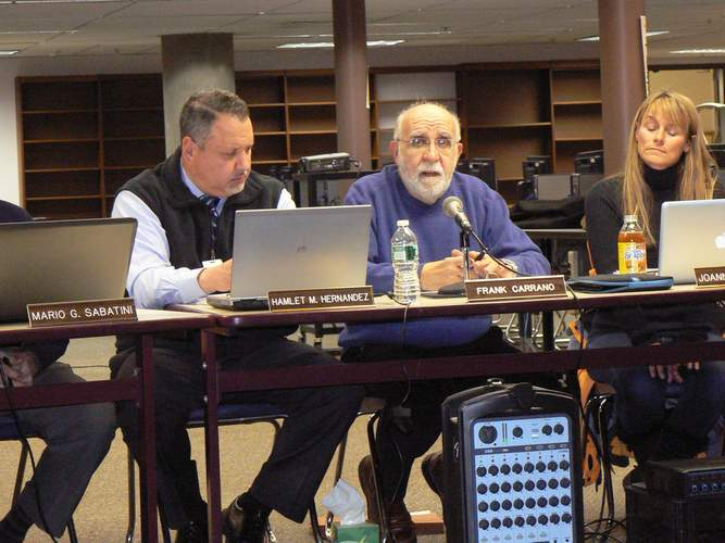 At the Feb. 6 budget workshop, BOE Chairman Frank Carrano (center) promotes cutting one of two positions built into the budget to support the requirments of an unfunded state mandate, saying he felt the district should