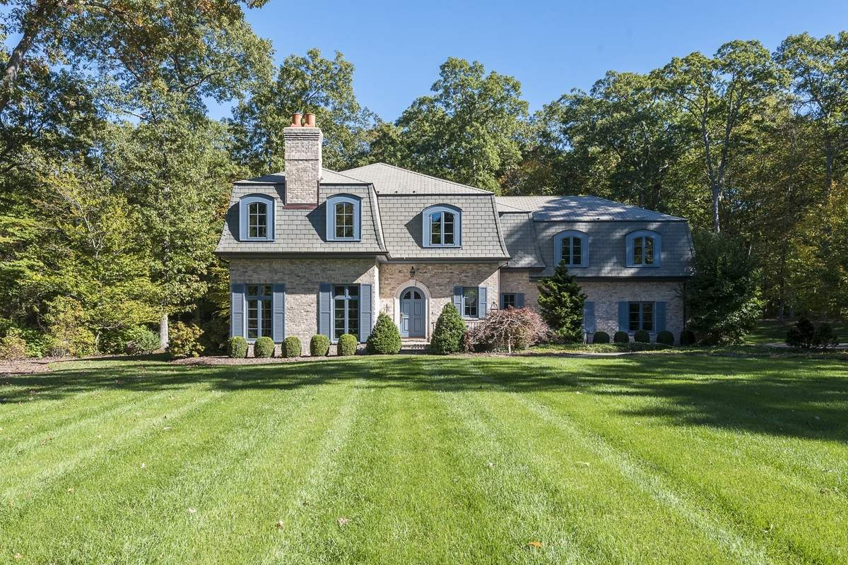 The French-château-style home is set in a large wooded lot.