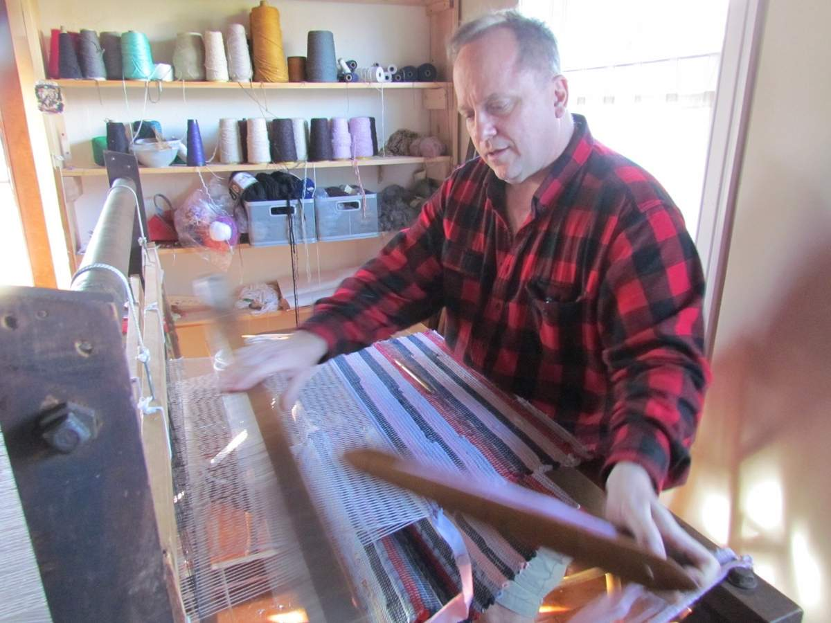 In his workshop in Branford's historic John Tyler House, Robert Aiudi's hands fly over the Union loom he uses to craft Colonial-style rag rugs, part of the unique inventory available at his temporary Christmas Shoppe in the house. Aiudi invites the public to visit the shop this holiday season and to enjoy an Open House, with demonstrations, on Sat. Dec. 10, from 11 a.m. to 5 p.m. Photo by Pam Johnson/The Sound