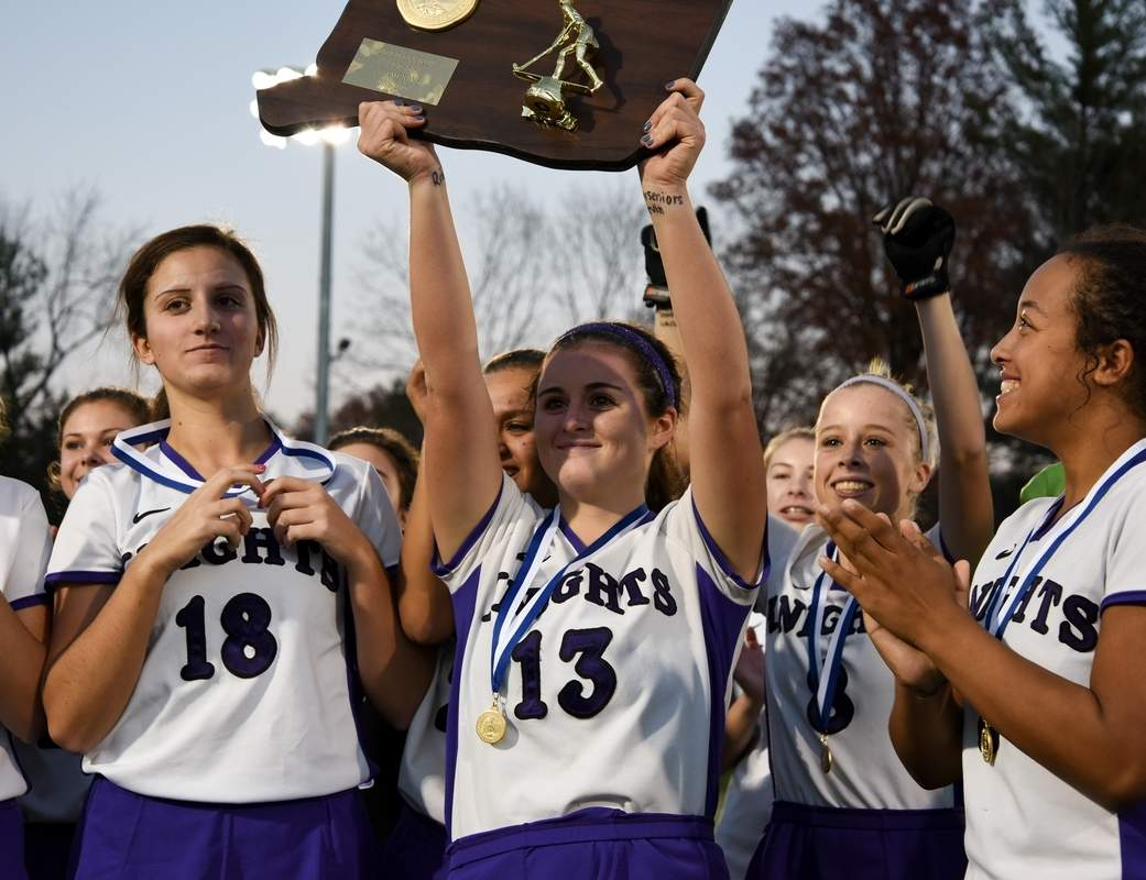 Senior Alexa Mulvhill hoists up the Class S state championship plaque after the Westbrook field hockey team played Haddam-Killingworth to a 1-1 tie in the final to share the title with the Cougars. Pictured on Mulvihill's left are Lauren Kane and Zoe Ehlert and on her right are fellow teammates Avery Baumann and Biance Ferrucci.  Photo by Wesley Bunnell/ Harbor News
