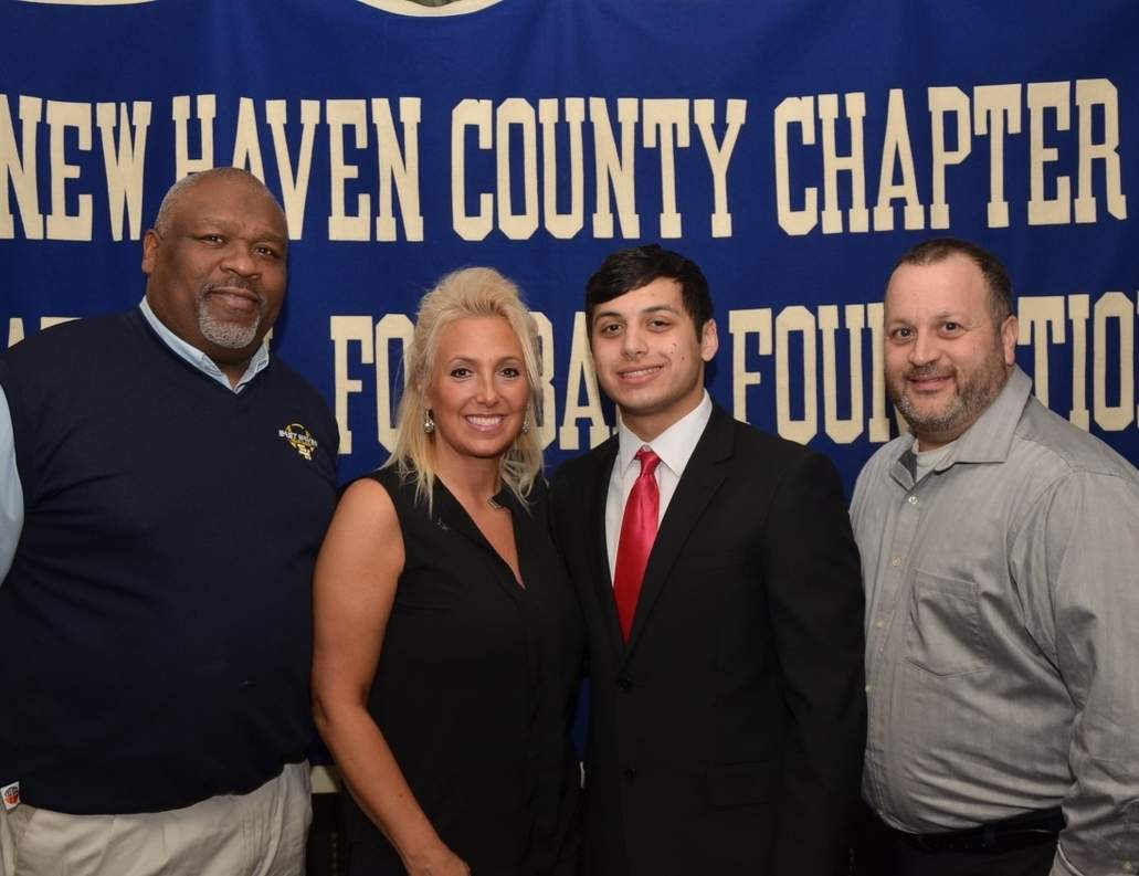 Dominic Manna stands between his parents Joanna Hall and Michael Manna with East Haven football coach Melvin Wells (left). Photo courtesy of Bill O'Brien