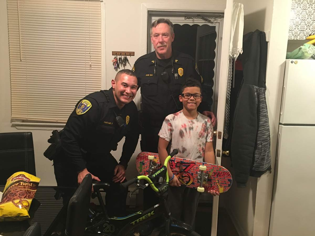 Clinton police officers Adrian Santiago, left, and Joseph Popovich, right, recently delivered presents for Kevyn Amorim Torre's 10th birthday. Through actions such as this and his frequent role as translator for speakers of Spanish, Italian, and Portuguese, in his five years on the force Adrian has become a critical part of his hometown community and his hometown police department. Photo courtesy of Susan Wallace