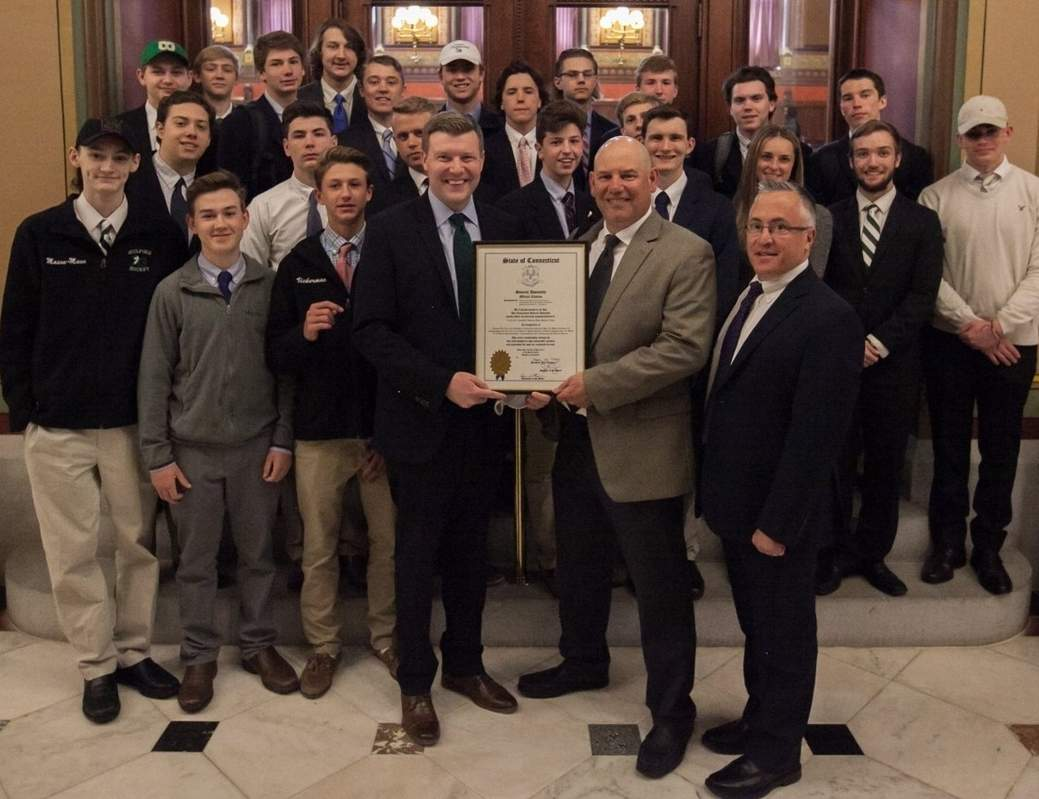 State representatives Sean Scanlon (D-98) (left) and Vincent Candelora (R-86) (right) present Guilford boys' ice hockey Head Coach Ralph Russo (center) and his team with an official citation marking the Indians' Division II state title this winter. Photo courtesy of Lorri Hahn