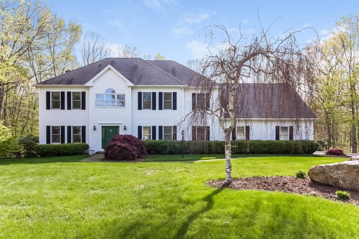 Two acres of manicured lawn and light woods surround this quiet Madison home.