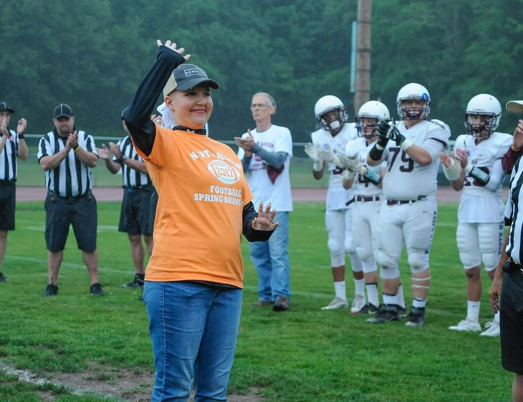 Amelia DePino is all smiles as she waves to the crowd prior to the North Haven football squad's 13th annual Spring Brawl fundraiser. DePino, a member of North Haven's senior class, was diagnosed with leukemia in January, and all the proceeds from this year's Spring Brawl will go toward her and her family in DePino's battle against the disease. Photo by Kelley Fryer/The Courier