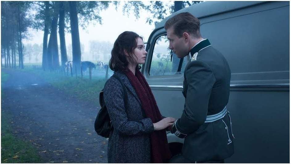 Mieke (Lily James) and Stefan (Jai Courtney) steal a moment together in the World War II drama, The Exception. Photo copyright A24