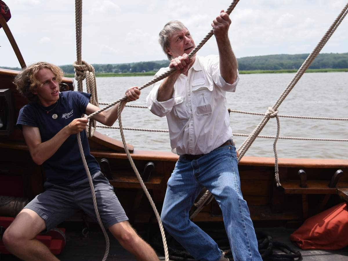 The Onrust, a historic reproduction a boat from 1614 docked at the Connecticut River Museum, for the summer, sets sail three times a day from Thursdays through Sundays.  Crew Roald Sovorne gets a hand from Doug Montgomery setting the main sail, as the Onrust heads up the Connecticut River.