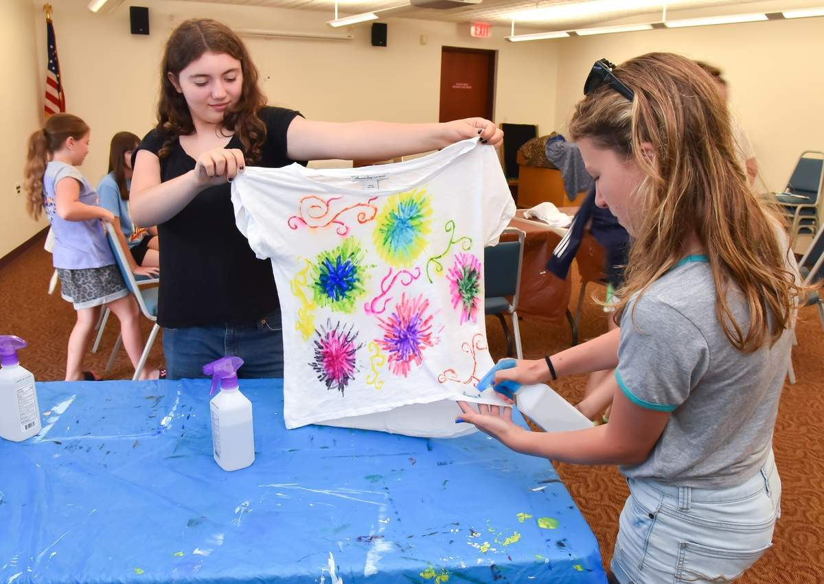 The North Haven Memorial Library's Creativity Club held a sharpie tie-dye in  event for kids in the community room. Genevieve Peters holds up Jocelyn Nutile's T-Shirt for her while she sprays the design.