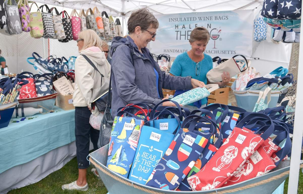 A beautiful weekend to shop at the 54th annual Old Saybrook Chamber of Commerce Arts and Crafts Festival. Lisa Carruthers and Pat Leete check out the insulated wine bags.