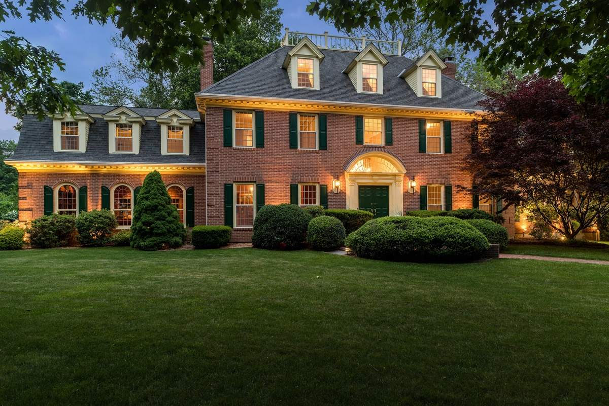 Thoughtful landscaping, including lighting and masonry, show this Wickford Place home to its best advantage.