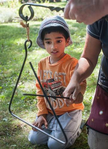 On Saturday September 9th the Hyland House Museum hosted an introduction to 18th-century blacksmithing demonstration.    Three-year-old Zan Perera rings a iron triangle, a dinner bell.        The Museum is fundraising to raise a new roof. For more information go to www.hylandhouse.org
