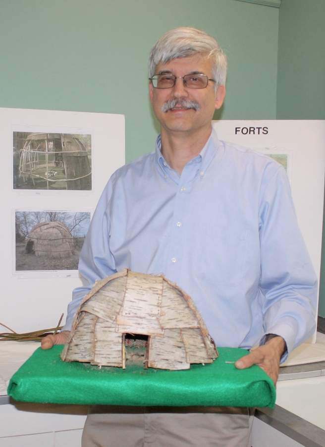 Some historians spend all their time poring over texts; others take a more hands-on approach. Rich Kalapos, Deep River's town historian, does a bit of both in his research on local history (he's displaying a model wigwam he crafted almost completely after original methods). Photo by Rita Christopher/The Courier