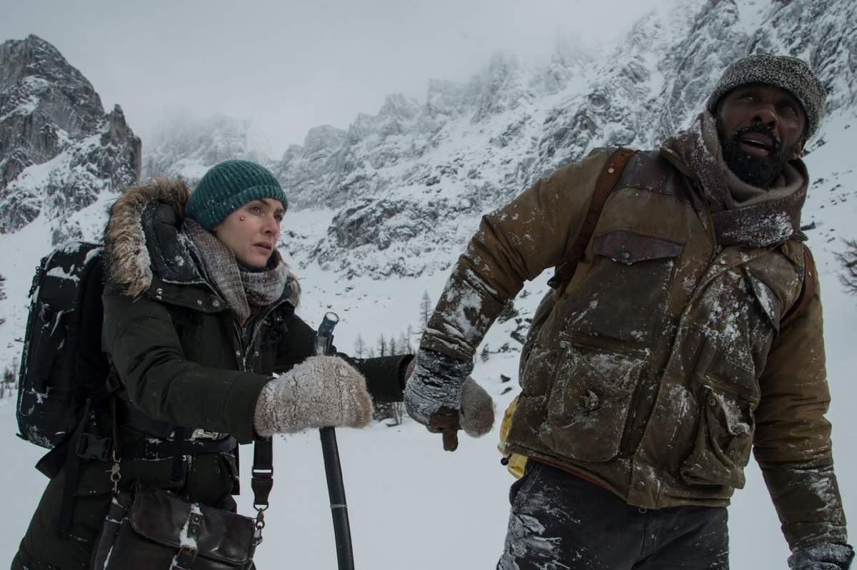 Alex Martin (Kate Winslet) and Ben Bass (Idris Elba) make their way over the mountains to find help as the only survivors of a plane crash in the romantic drama, The Mountain Between Us.   Photo by Kimberley French/Copyright TM & copyright 2017 Twentieth Century Fox Film Corporation