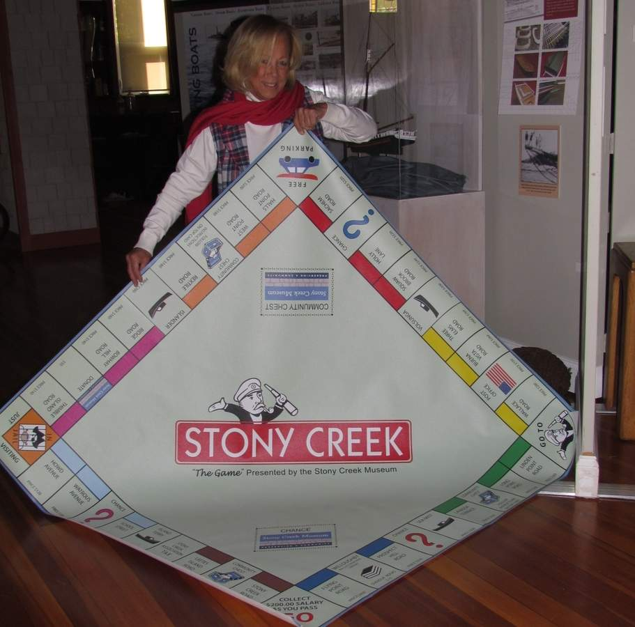 At the Stony Creek Museum, Jennifer Walker shares a peek at the giant game board that will be the center piece of Stony Creek Museum Game Night, a fun fundraiser coming to the museum on Friday, Nov. 3. Photo by Pam Johnson/The Sound