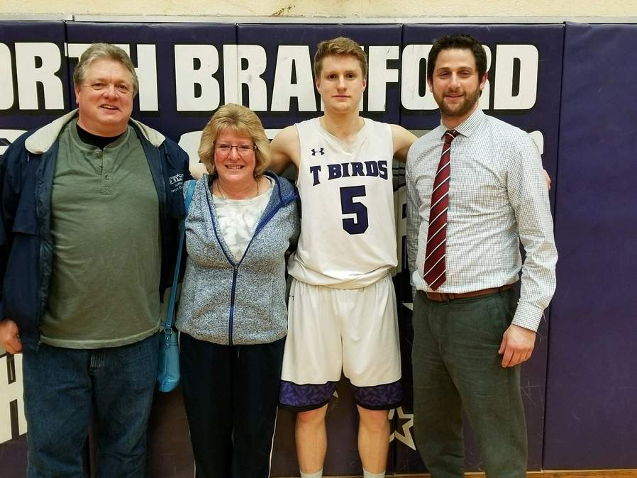 North Branford senior Brett Lequire became the top scorer in North Branford boys' hoops history when the T-Birds defeated Shepaug Valley 70-56 in the second round of the Division V State Tournament on March 8. Pictured are Lequire's parents, Curt and Michele, with Lequire and Head Coach Dave Parness. Photo courtesy of Nick DeLizio