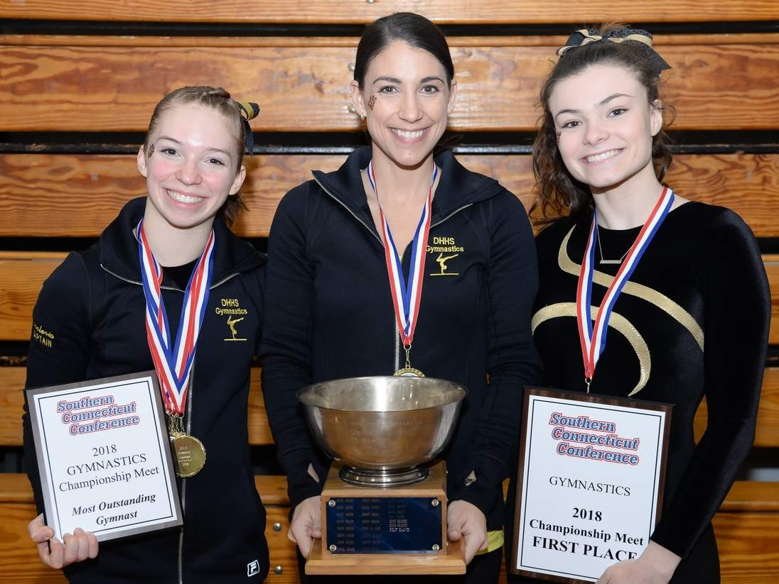 The Hand gymnastics team took first place at the SCC Championship for the 10th year in a row this winter. Pictured with the Tigers' postseason hardware are senior captain Eric Naclerio, Head Coach Kelly Smith, and senior captain Delaney Skelly. Photo by Kelley Fryer/The Source