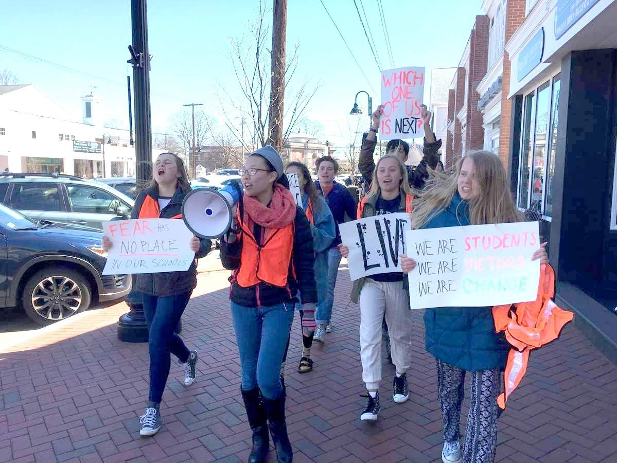 Several dozen students protested against gun violence and advocated for change on April 20, marching from the Madison Town Green through Madison's business district, holding signs and chanting. Photo by Pem McNerney/The Source
