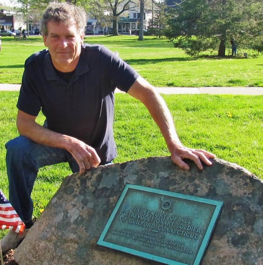 Shown here with a stone and plaque on the town green commemorating Guilford Revoluntionary War soldiers; Craig Reynolds has helped the 6th CT Regiment spearhead a new Revolutionary War plaque, to be unveiled May 19 at Sachem's Head Harbor, the site of the launch of Meigs' Raid, a critically successful battle early in the war.  Pam Johnson/Guilford Courier