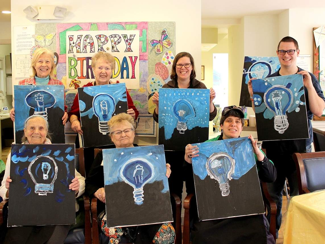 Participants in Vista Life Innovations and Strong House Adult Day Center Light It Up Blue painting activity display their completed works. From left are (seated) Florence Maciolek, Gloria Neri, and Leslie Strasser and (standing) Mary Jane Gardner, Claire Demery, Rachael Hoskin, and Matt Jacques. Photo courtesy of Vanessa Pereira
