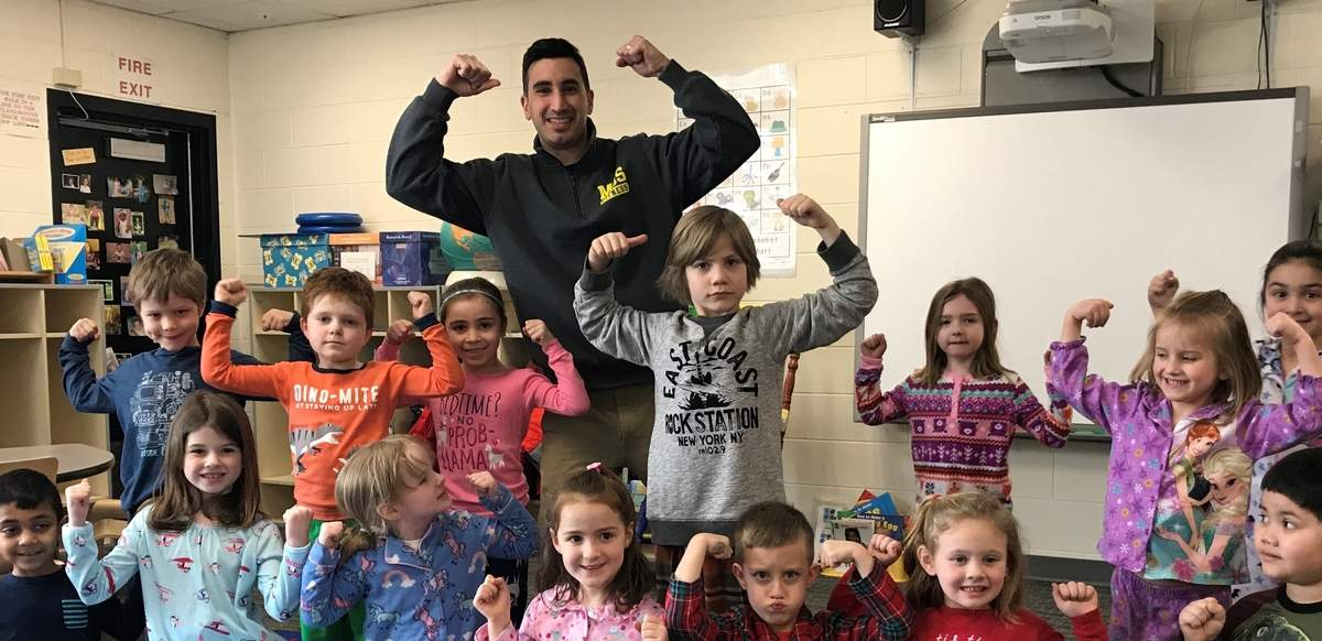 At Melissa Jones School, physical education teacher Derek DeLucia pumps kids up with Fitness Fridays and other fitness fun that helps keep them healthy and motivated to learn. He's shown here after a session with kindergarteners in the classroom of teacher Shauna Panella. Photo by Pam Johnson/The Courier