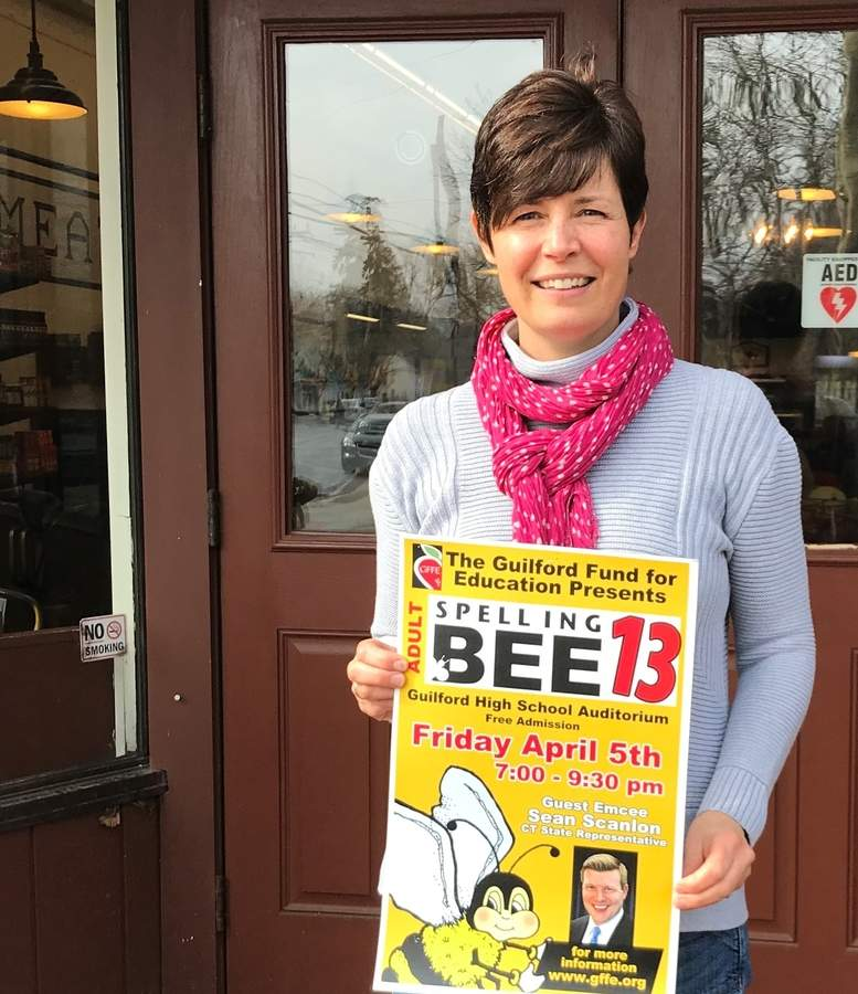 Laurie Dray is building a buzz around the 13th annual Guilford Fund for Education (GFFE) Adult Spelling Bee, which takes place Friday, April 5 at Guilford High School. She's shown here outside The Marketplace at Guilford Food Center, the providers of food for sale at the bee to benefit GFFE. Photo by Pam Johnson/The Courier
