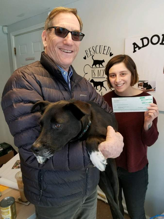Andy Teran of Coldwell Banker Residential Brokerage in Old Saybrook and his rescue dog Tucker present a $550 check to Valley Shore Animal Welfare League Shelter Manager Catie Moore.   Photo courtesy of Lisa Martin