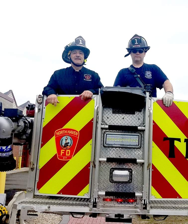 Fire Commissioner Peter Criscuolo (left) gets a lift from firefighter Dan Spetland to test the 100-foot reach on the North Haven Fire Department's new tower truck.  Photo by Nathan Hughart/The Courier