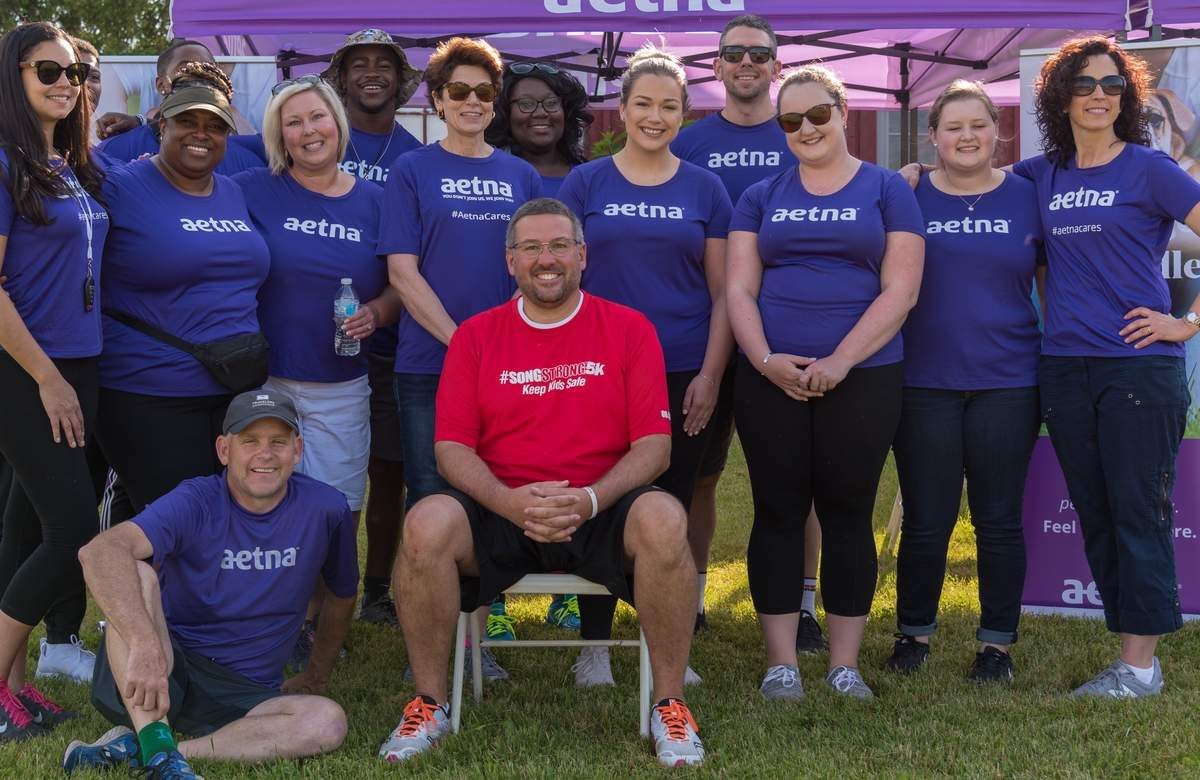 As co-race director of #SongStrong5K, one of the first things Scott Markovich (center, in red) did was to bring in his company, Aetna, as the title sponsor. Here, he's shown with members of his team who flew in from points across the country to volunteer at the inaugural race event in 2018. Soon, his team, together with many other volunteers, sponsors, businesses, organizations, and the Guilford community, will once again rally around the mission and message of the Ethan Miller Song Foundation at the second annual #SongStrong5K, coming to the Guilford fairgrounds Saturday, June 8. Photo courtesy of Scott Markovich
