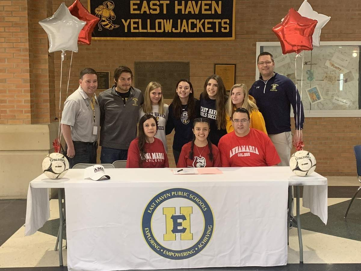 East Haven's Ashlie Rivera signed on to play soccer at Anna Maria College in Massachusetts. Pictured are (front) Rivera's mother, Rose Rivera, with Rivera and her father, Victor Rivera; along with (back) East Haven High School Principal Vin DeNuzzo, girls' soccer Head Coach Jake Hackett; Rivera's teammates, Emily Pycela, Aimee DiVerniero, Christina Fazzino, and Kate Pycela; and East Haven Athletic Director Anthony Verderame. Photo courtesy of Anthony Verderame