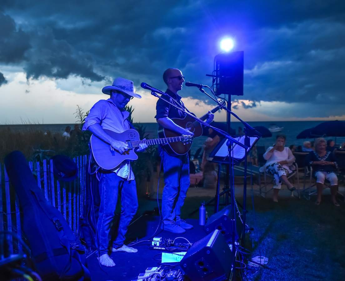 A dramatic sunset  with a storm front passing over the Madison Beach Hotel, as the Grassy Strip Music Series with Michael Cleary and Lee Sylvestre played  not missing a beat. Photo by Kelley Fryer/The Source