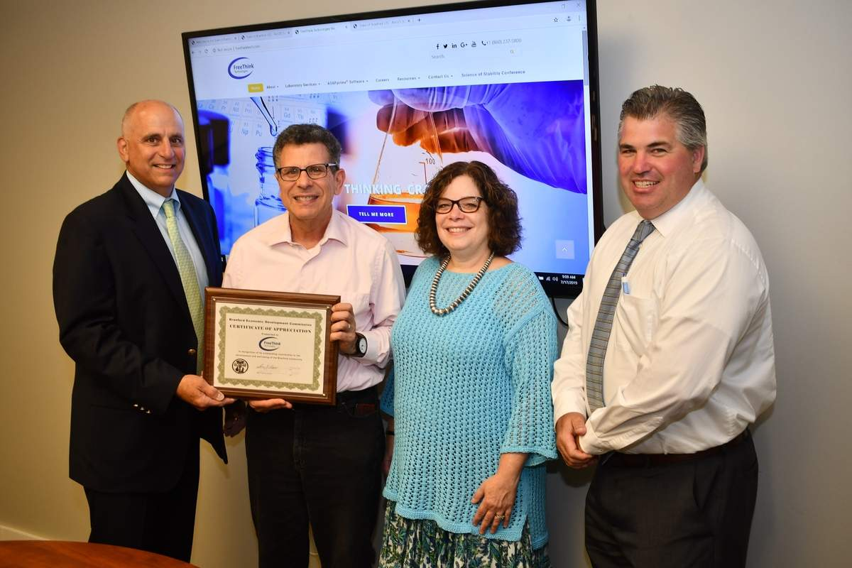 FreeThink founder and CEO Ken Waterman and FreeThink Chief Science Officer Alisa Waterman (center) accepts Business Recognition Award honors from (from left) Economic Development Commission Chair Perry Maresca and First Selectman Jamie Cosgrove (R). Photo by Bill O'Brien