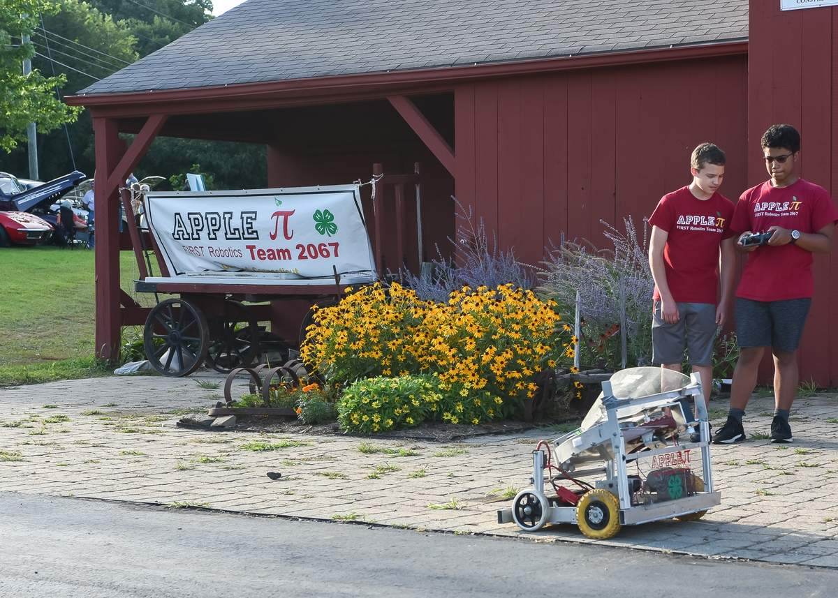 Guilford High Apple Pi Robotics Team held a Cruise Night Car Show at BishopþÄôs Orchard on a beautiful Thursday evening. Ian Lataillade and Luke Romblad drive around one of their older robots at the Cruise night. Photo by Kelley Fryer/The Courier