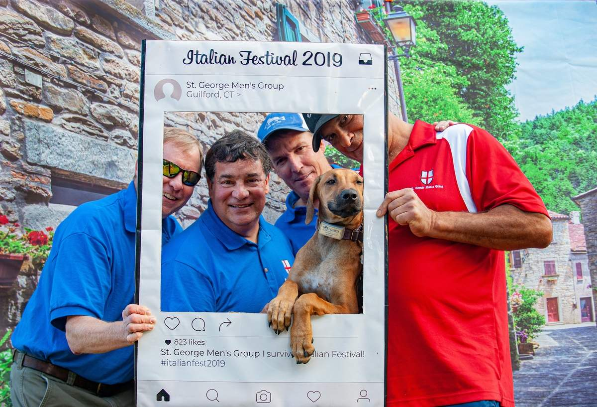 St. George Church held their Italian Festival 2019 this past weekend behind the church. The event celebrates Italian Culture while raising money for the Guilford Community Fund.  Members of the St George Men's Club, Tod Rake, James Mancini, event chair, Jonathan Wallace, Jeff Trobetta and Cora a four-month-old Rhodesian Ridgeback pose in front of an Italian backdrop to promote their cause on social media.  Photo by Susan Lambert/The Courier