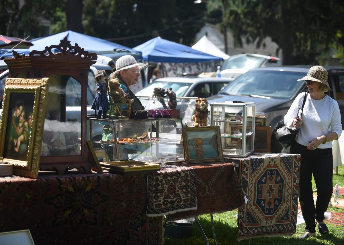 Madison Historical Society held its 48th annual Madison Antiques Fair on the Madison Green, Saturday. Kim Brewer talks with Jane Grant as she looks over the items for sale. Photo by Kelley Fryer/The Source