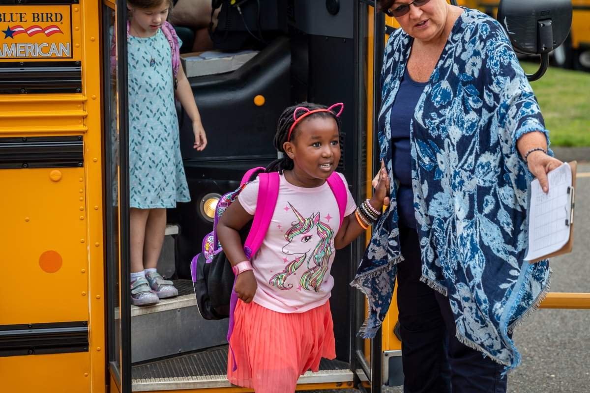 Students went back to school at Clintonville Elementary School in North Haven on Wednesday, August 28, 2019. Some kids were returning, while others were going to school for the first time. Ava Muteru gets off the bus ready for her first day of first grade. Photo by Meglin Bodner/The Courier