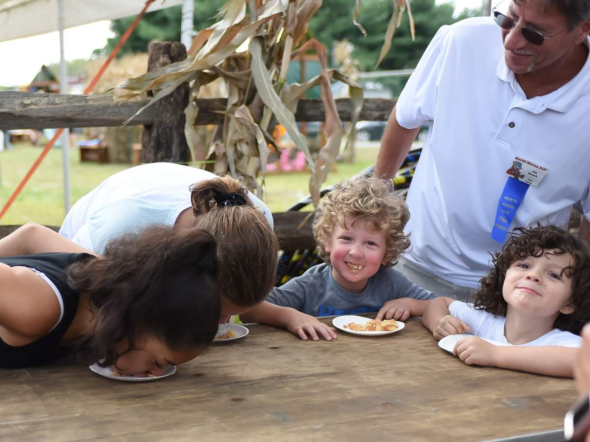 The 77th annual North Haven Fair took place Sept 5th through the 8th at the North Haven Fairgounds. Jim Munck watched over the  pie eating contest, Angelique Flores, Haley Ardito, Everett Quirk-Orowson and Aiden Faye  eat the apple pie. Photo by Kelley Fryer/The Courier