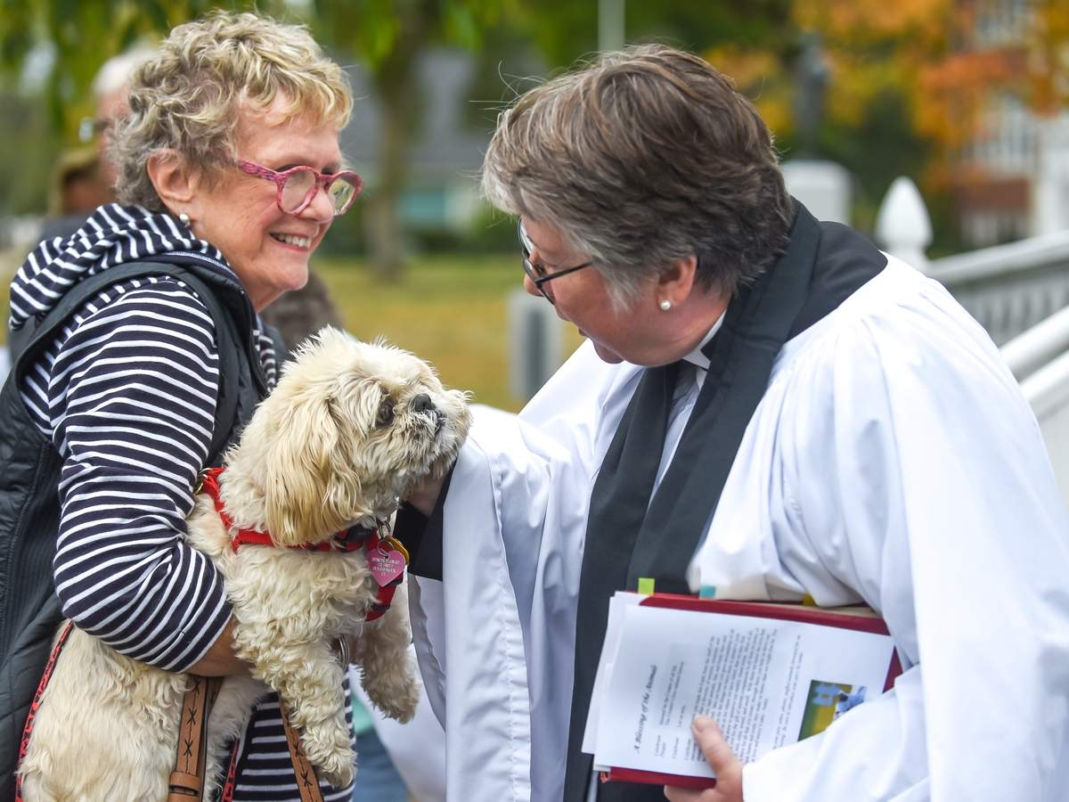 Blessing of the Animals took place at Episcopal Church of the Holy Advent, in Clinton. The blessing was lead by Priest, Diana Rogers, and Curate,  Dana Stivers who had everyone gather with their pets to the church front yard for a blessing in the manner of St. Francis of Assisi. Diana Rogers blesses Katie held by Karen Stickney. Photo by Kelley Fryer/Harbor News