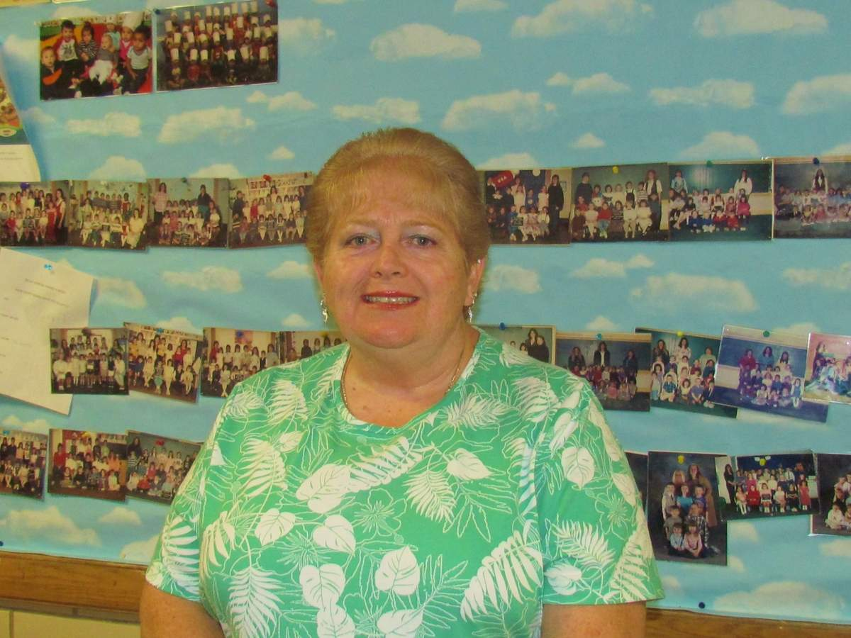Karen McMinn TenBroeck stands at Branford Early Learning Center's (BELC) Wall of Fame, where photos include hundreds of children she's taught in her 40 years as a BELC educator. Photo by Pam Johnson/The Sound