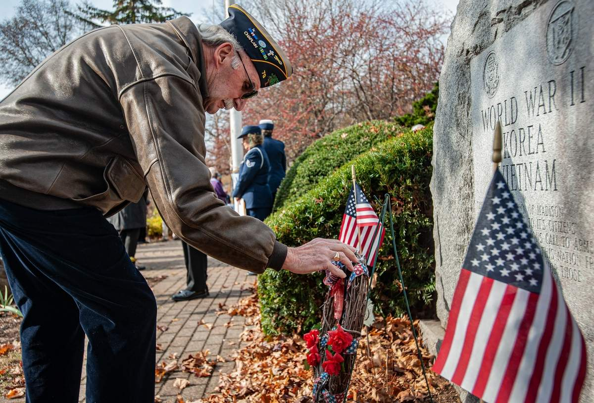Madison marked Veterans Day with a ceremony to honor those who served Monday November 11th on the town green.  Veteran Leon Chmielewski lays a wreath on hte World War II, Korea, Vietnam monument.   Photo by Susan Lambert/The Source