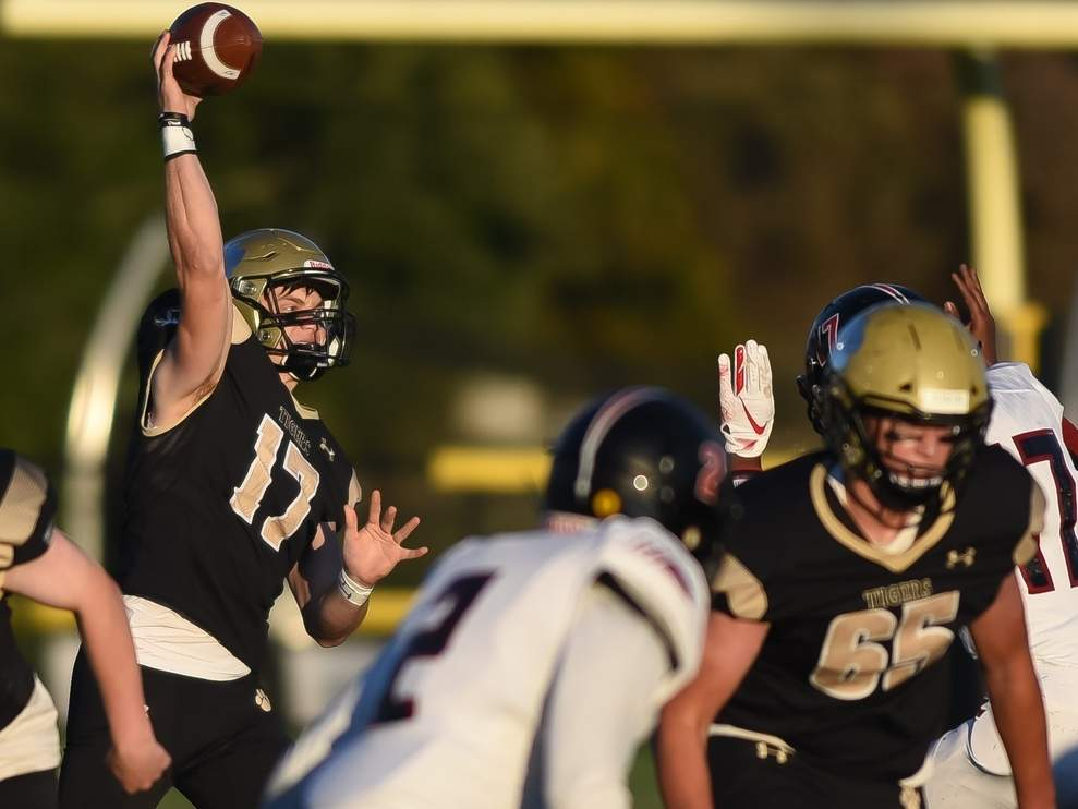 Phoenix Billings tossed four touchdown passes to lead the Hand football team to a 61-6 win in Guilford on the night before Thanksgiving. The Tigers recorded their second-straight undefeated regular season by going 10-0 this fall. Also pictured is No. 65, Sander Coscia. File photo by Kelley Fryer/The Source