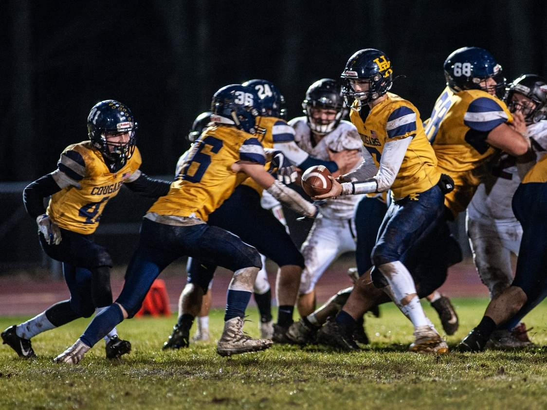 Alex Riccitelli (right) hands the ball off to Ryder Wink during the H-K football team's annual game against Valley Regional-Old Lyme on Nov. 26. The Cougars took a 20-2 defeat to the Warriors in the contest. Pictured on the left for H-K is No. 41, Dalton Modehn. Photo by Susan Lambert/The Source