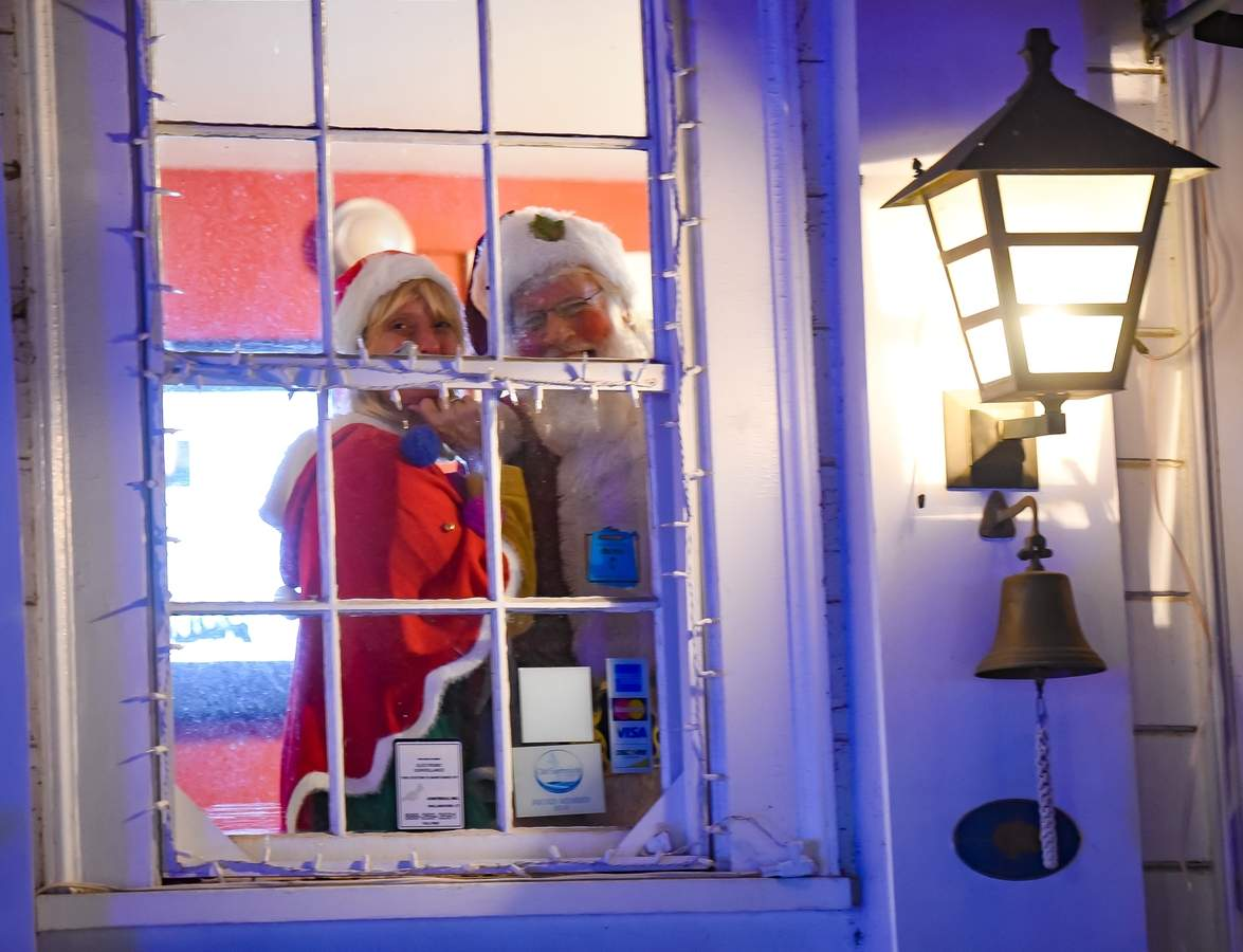 A cold clear Saturday  night for the Ivoryton Illuminations, with crowds filling the streets and the Ivoryton Playhouse grounds listing and singing along with choirs, as they waited for Santa's arrival.  IvorytonþÄôs executive/artistic director Jacqueline Hubbard and Santa peep through the window at the playhouse. Photo by Kelley Fryer/The Courier