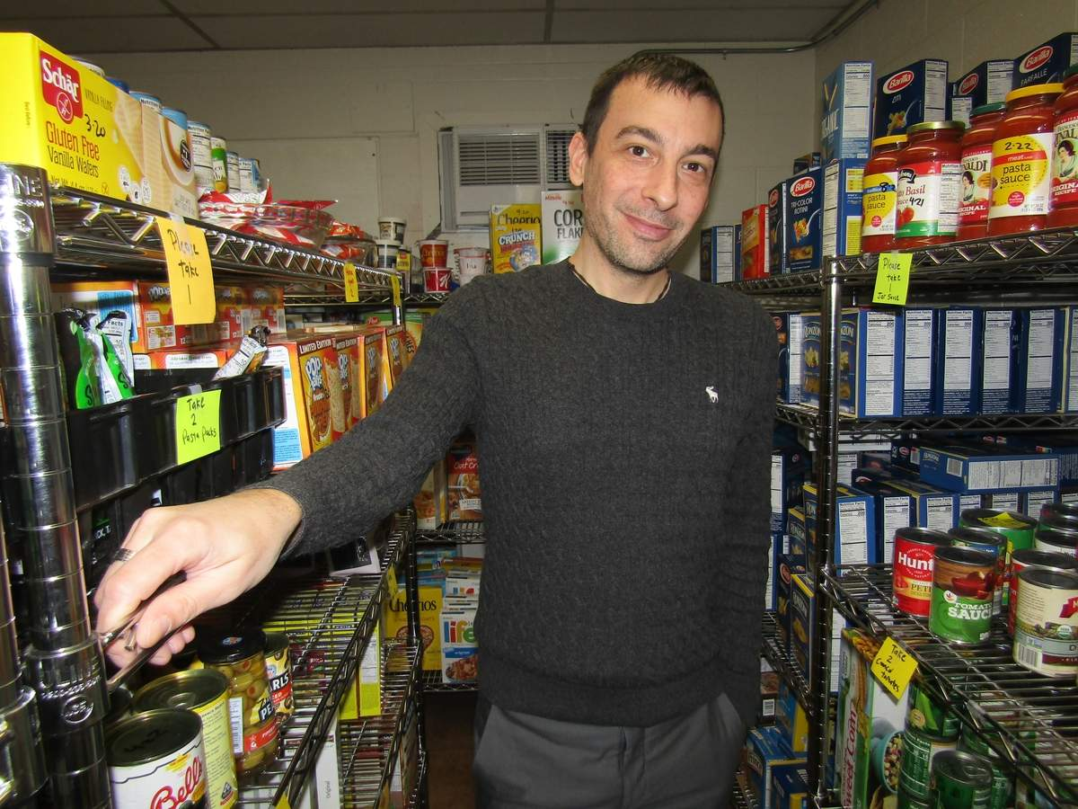 Robert Snurkowski is happily settling into his role as community services senior clerk for the Town of North Haven, coordinating stock at the food pantry (shown here) as well as helping neighbors in need address heating needs for the winter season.  Photo by Elizabeth Reinhart/The Courier