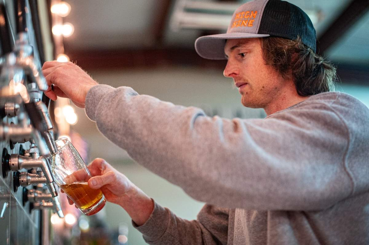 High Nine Brewery bartender Spencer Waldron pours a draft. The brewery is named after Waldron who lost a finger in his youth. He's known for giving high nines rather than a hgh fives.  The High Nine Brewery opened their doors mid- November 2019.  They offer a diverse tap list and are open Wednesdays through Sundays.  Photo by Susan Lambert/The Courier