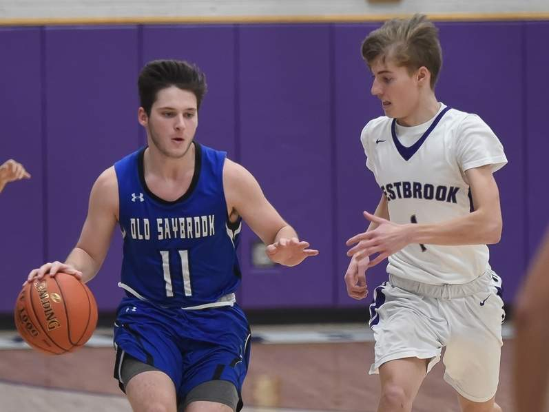 Senior captain Davis Brown (left) and the Old Saybrook boys' basketball squad lost a 58-42 contest against Coginchaug on Jan. 16. Brown scored seven points on the night. Also pictured is Westbrook's Jesse Whitney. File photo by Kelley Fryer/Harbor News