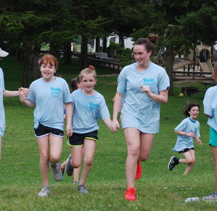 Shown here helping 4th grade girls cross the finish line at the 2019 Girls Coach, Girls Run (GCGR) 5K Fun Run, Tara Henry (right) has experienced the empowerment of the Women & Family Life Center (WFLC) program in all of its stages—as a 4th-grade participant, an 8th-grade coach-in-training, and high school head coach. GRGC is now branching out to Branford, where Tara will be the head coach for a group that will meet at Tisko Elementary School beginning in April. Photo courtesy of the Women & Family Life Center