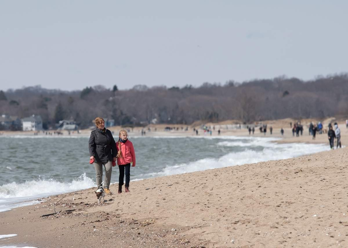A beautiful sunny day brought people out to Hammonasset Beach State Park, Madison on Saturday afternoon. Due to the coronavirus  (COVID- 19 ), Meigs Point Nature Center was closed. Sybil and daughter Finja Saewe and dog Lolya took a walk along the beach to get some fresh air and sunshine.  Photo by Kelley Fryer/The Source