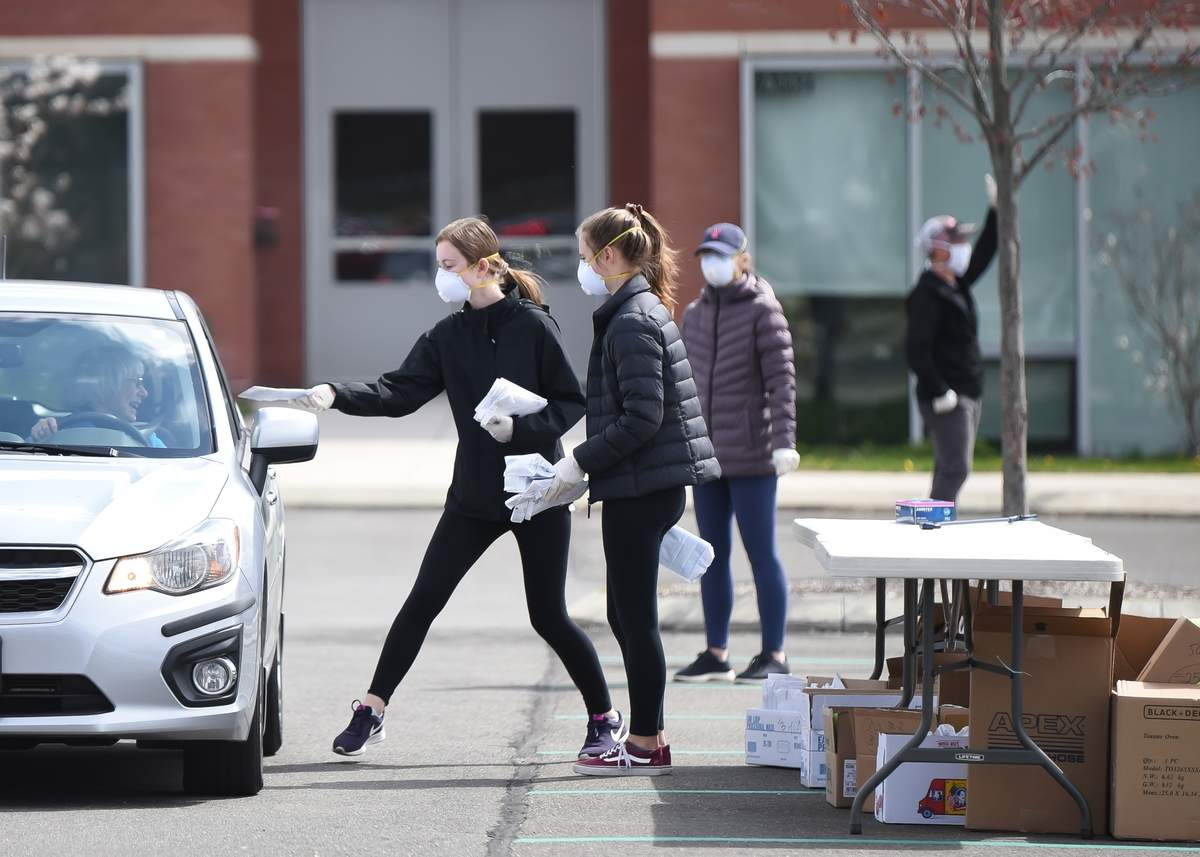 The Town of Guilford, set up a mask distribution site at the Guilford High School on Tuesday April 28th at 10am with volunteers handing out pre packaged masks in envelopes containing 2 or 5 masks to a steady stream of  people driving through. Jennifer Mullett and daughters Emma and Riley work together to distribute masks.   Photo by Kelley Fryer/The Courier