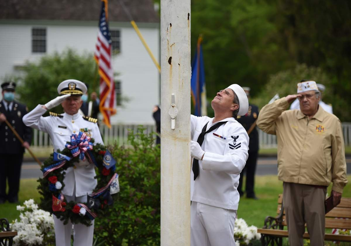 A small gathering for a Memorial Day ceremony on the Madison Green was lead by outgoing American Legion Post 79 Commander Donna Farrell. The event was live-streamed by Abigail White and Steve Fuest from the Madison Cable Access Group.     Fillmore McPherson,  Larry Brundrett Commander VFW Post  2096 Madison all salute as the flag is raised by Fred Muler.          Photo by Kelley Fryer/The Source
