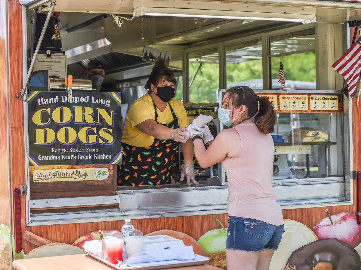 The Guilford Fairgrounds had a beautiful weekend to host a drive-through food truck festival. Christina Geremia picks up a corn dog from from Debbie Alduini and Jack Gregory. Photo by Kelley Fryer/The Courier